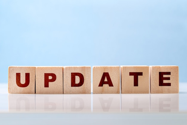 Het woord update is geschreven op houten blokken op een glanzend bureaublad op een blauwe achtergrond