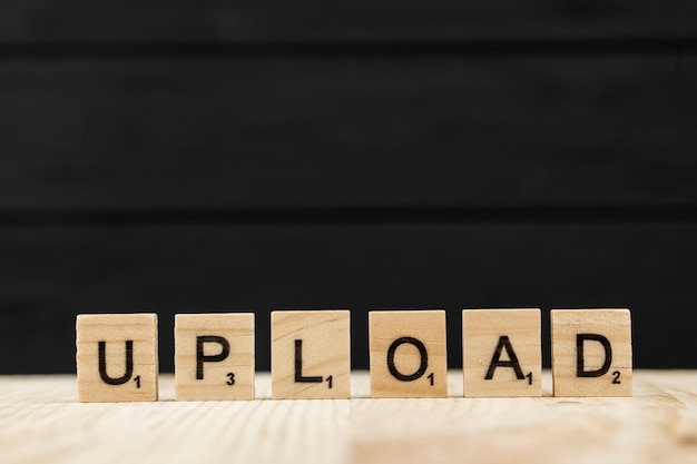 Het woord upload gespeld met houten letters
