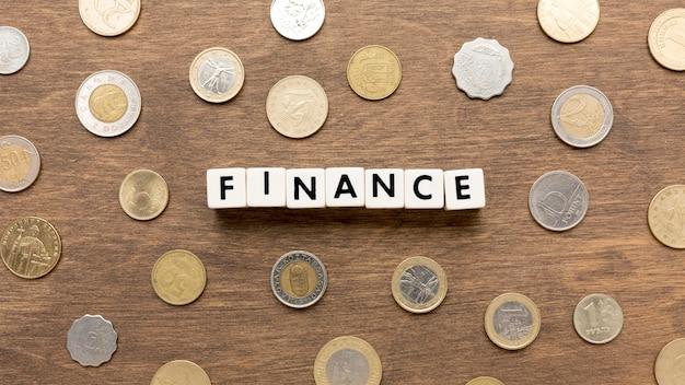 Het woord van financiën dat wordt geschreven graait in brieven en muntstukken