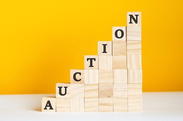 Het woord veiling is geschreven op een houten kubussen. blokken op een felgele achtergrond. bedrijfshiërarchieconcept en marketing op meerdere niveaus. selectieve aandacht.