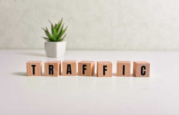 Het woord verkeer geschreven op houten kubussen met uitwisselingspictogrammen op geel