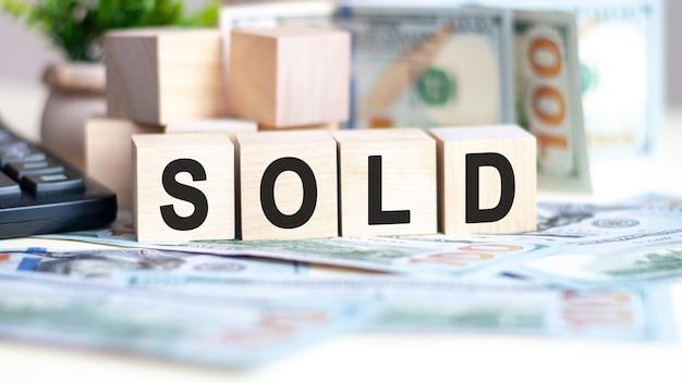 Het woord verkocht op houten kubussen op bankbiljetten en rekenmachine