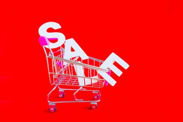 Het woord verkoop in witte volume letters en een metalen winkelwagentje naast een rode achtergrond.
