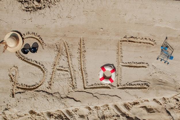 Het woord verkoop is geschilderd op het zand