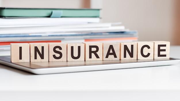 Het woord verzekering is geschreven op houten kubussen die op een notitieblok staan, in het oppervlak een stapel documenten