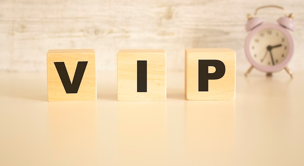 Het woord vip bestaat uit houten blokjes met letters, bovenaanzicht op een lichte achtergrond. werkruimte.