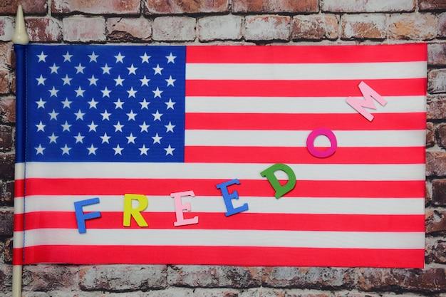 Het woord vrijheid is bekleed met veelkleurige letters op de amerikaanse vlag tegen een oude bakstenen muur