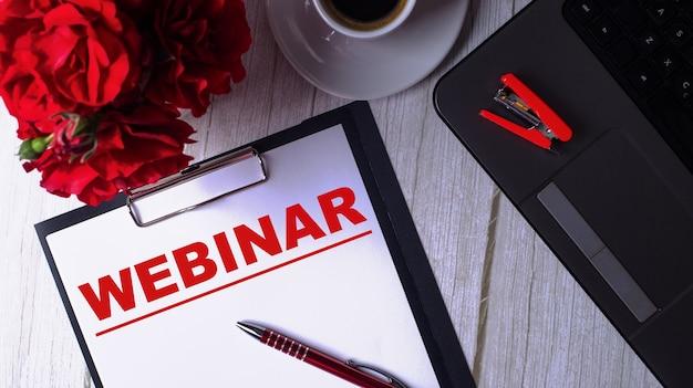 Het woord webinar is in het rood geschreven op een wit notitieblok naast een laptop, koffie, rode rozen en een pen.