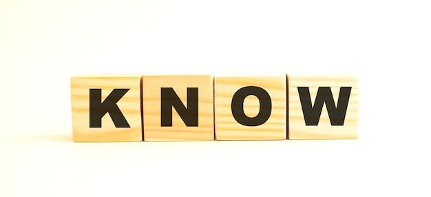Het woord weet. houten kubussen met letters geïsoleerd op een wit oppervlak.