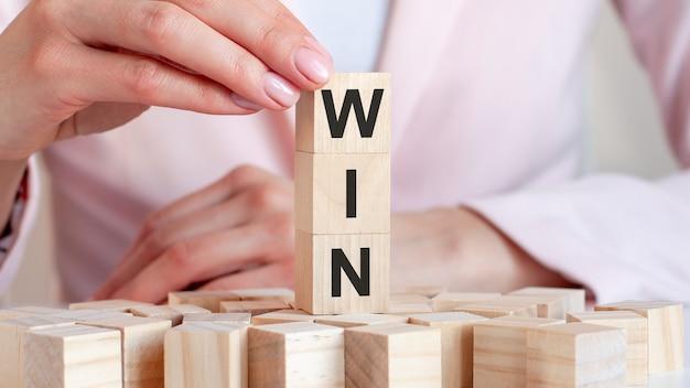 Het woord winnen op een houten stuk speelgoed blokken met dameshanden, bedrijfsconcept.