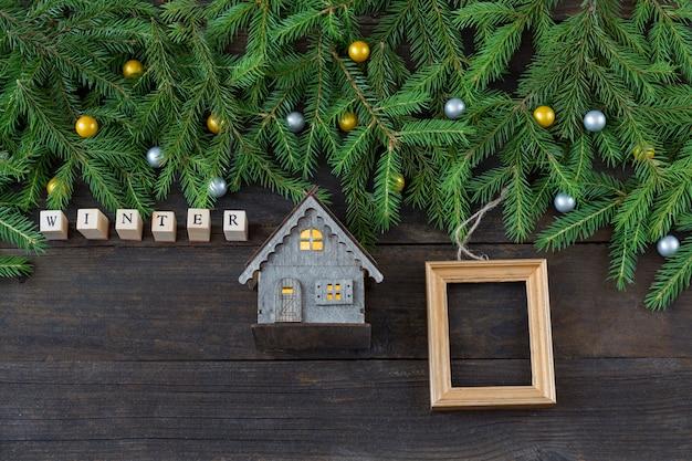 Het woord winter van houten letters, een klein houten huis en een houten frame voor een foto