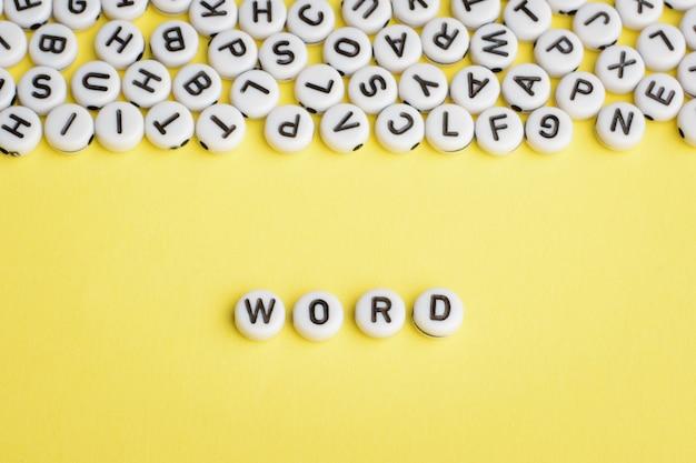 Het woord word gemaakt van witte plastic blokken op geel met veel letters erop