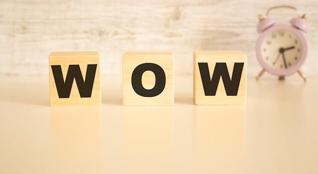 Het woord wow bestaat uit houten kubussen met letters, bovenaanzicht op een lichte achtergrond. werkruimte.