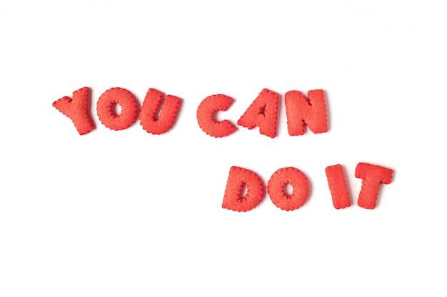 Het woord you can do it gespeld met roodgekleurde alfabetvormige koekjes