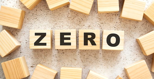 Het woord zero bestaat uit houten kubussen met letters, bovenaanzicht op een lichte achtergrond. werkruimte.
