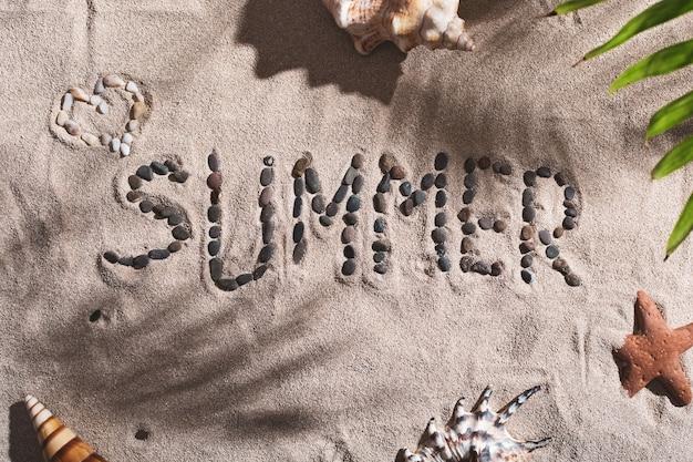 Het woord zomer is aangelegd met stenen op een zandstrand in de zomer tussen schelpen