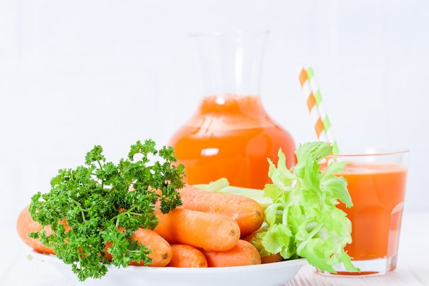 Het wortelsap in mooie glazen snijdt oranje groenten en groene peterselie op witte houten achtergrond