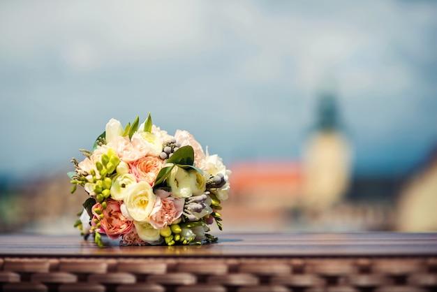 Het zachte huwelijksboeket van witte en roze pioenen ligt op een lijst