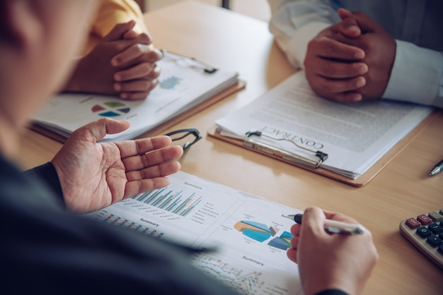Het zakelijke team werkt aan boekhoudkundige documenten en het team werkt samen om het werk te presenteren en het probleem op te lossen.