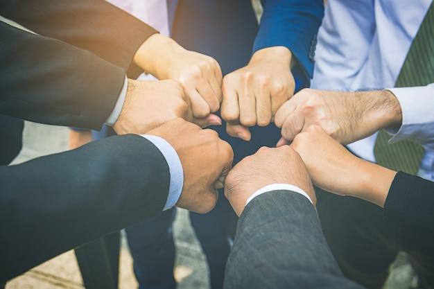 Het zakenlui dient vuisten in cirkel, bedrijfs en groepswerkconcept in
