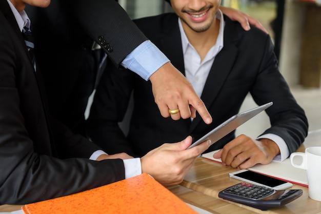 Het zakenmanenteam bespreekt plan door tablet