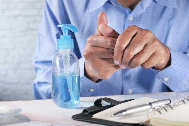 Het zakenmanwerk in bureauruimte die handdesinfecterend middel gebruiken.