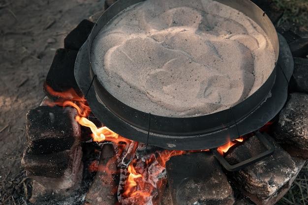 Het zand wordt op het vuur verwarmd om koffie te zetten