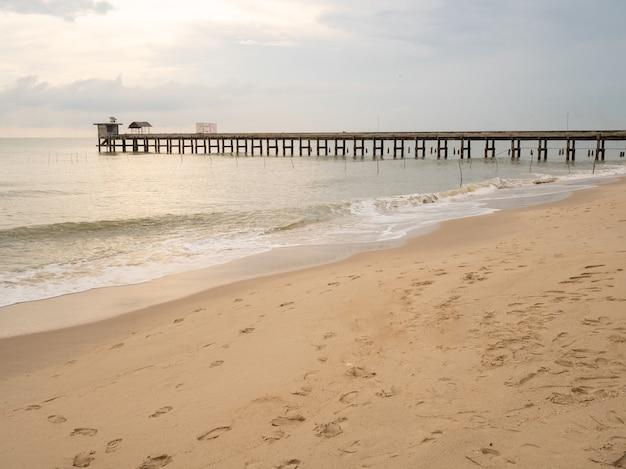 Het zandstrand van de zee heeft windgolven, er zijn stenen bruggen die in zee lopen