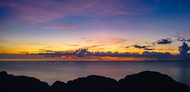 Het zeegezicht blauwe hemel van de schemering over de voorgrond van de kleurrijk en silhouetberg bij phi phi eiland thailand