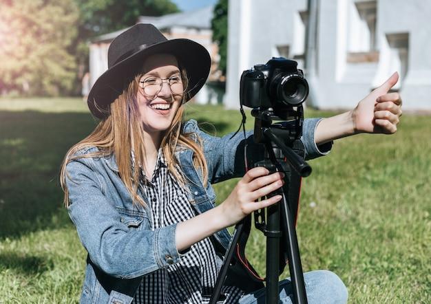 Het zeer gelukkige jonge meisje in een hoed maakt in openlucht foto op camera