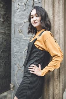 Het zekere aziatische meisje stellen, die trots kijken. straat portrat