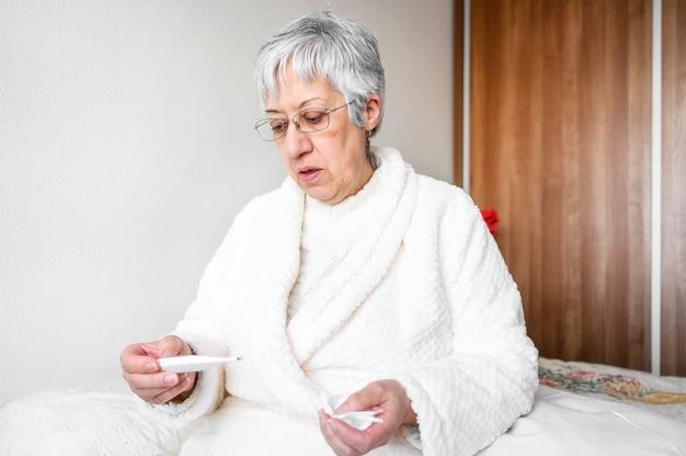 Het zieke hogere weefsel en de thermometer van de vrouwenholding zitten op bed.