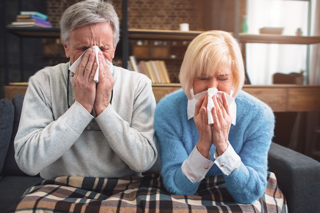 Het zieke paar probeert in het servet te niezen. ze werden verkouden