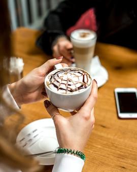 Het zijaanzicht een meisje drinkt cappuccino