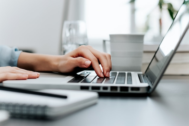 Het zijaanzicht en sluit omhoog van de handen van de vrouw typend op laptop toetsenbord.
