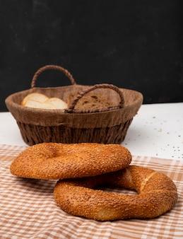 Het zijaanzicht van bagels op doek met mand van wit en roggebrood snijdt op witte oppervlakte en zwarte achtergrond met exemplaarruimte