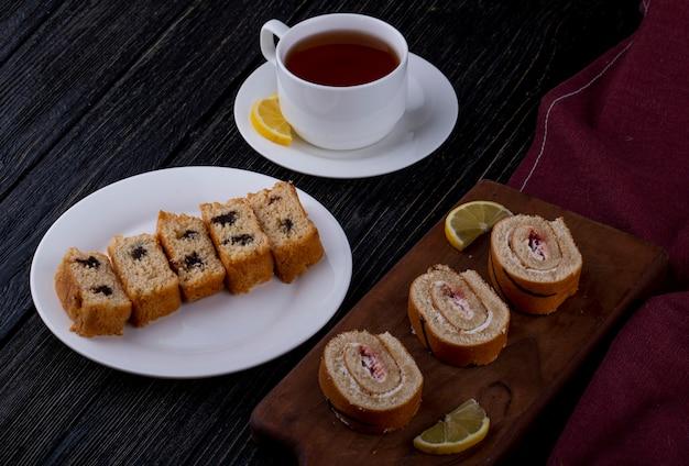 Het zijaanzicht van biscuitgebakplakken met chocolade en frambozenjam op een houten raad diende met een kop thee