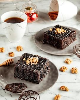 Het zijaanzicht van de cakes van de chocoladebrownie op plaat diende met thee op marmeren lijst