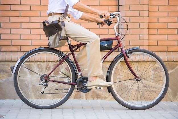 Het zijaanzicht van de mens berijdt fiets in de straat.