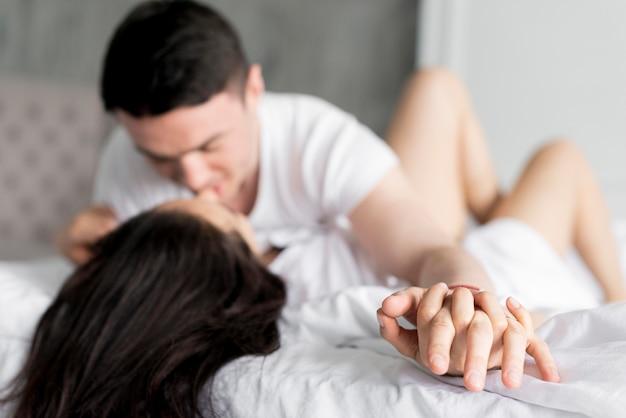 Het zijaanzicht van defocused paar dat vertrouwelijk in bed is