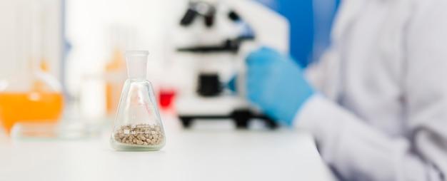 Het zijaanzicht van defocused vrouwelijke wetenschapper met laboratoriumapparatuur