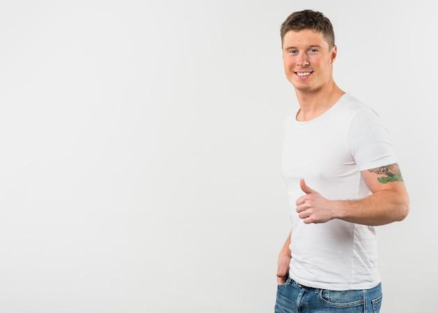 Het zijaanzicht van een glimlachende jonge mens die duim toont ondertekent omhoog tegen witte achtergrond