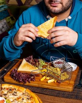Het zijaanzicht van een mens die clubsandwich eet diende met ketchup en frieten