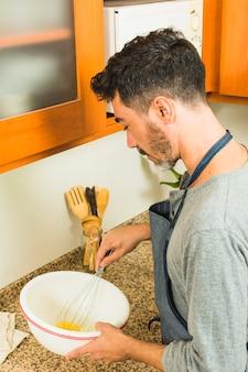 Het zijaanzicht van een mens die de eieren klopt met zwaait in het keukenteller