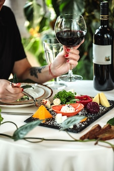 Het zijaanzicht van een vrouw die een glas wijn houden bij de lijst diende met kaasplaat