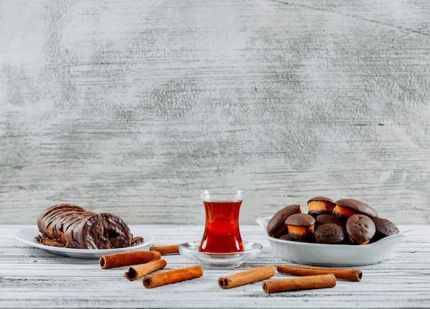 Het zijaanzicht van gebakjes over een scherpe raad en zakdoek en houten wit