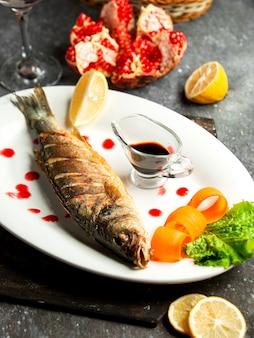 Het zijaanzicht van gebakken zeebaars diende met lemonnd narsharab saus op witte schotel op zwarte