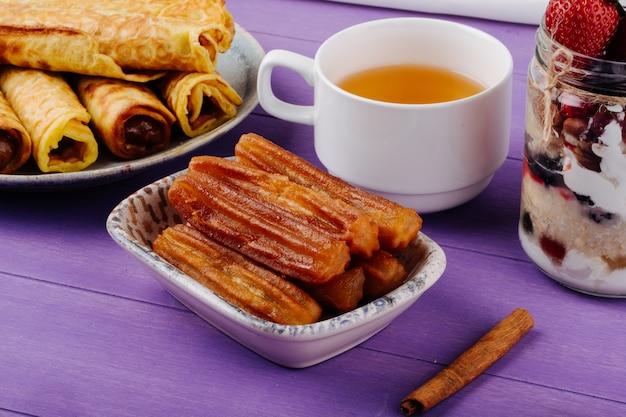 Het zijaanzicht van gebraden deeggebakje met honing diende met een kop groene thee en pijpjes kaneel op purpere houten lijst