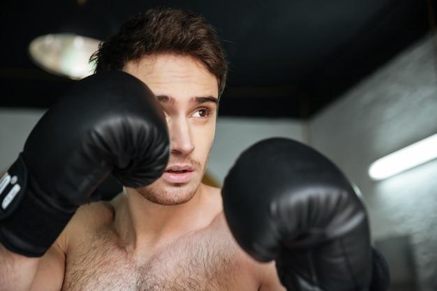 Het zijaanzicht van geconcentreerde mensenbokser met opgeheven dient handschoenen in die proberen te schoppen
