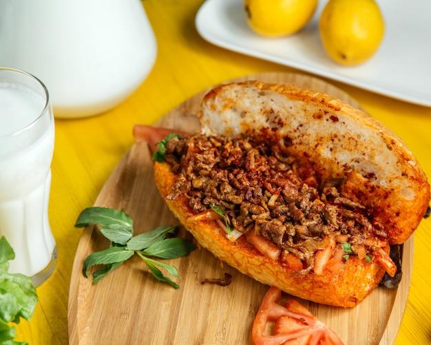 Het zijaanzicht van gehakt met groenten in brood diende met verse tomaten en citroen op houten raad